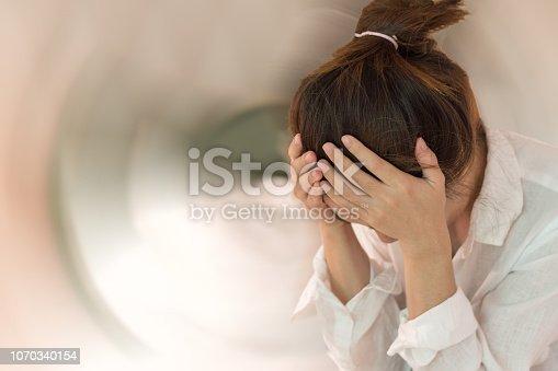 istock Vertigo illness concept. Woman hands on his head felling headache dizzy sense of spinning dizziness,a problem with the inner ear, brain, or sensory nerve pathway. 1070340154