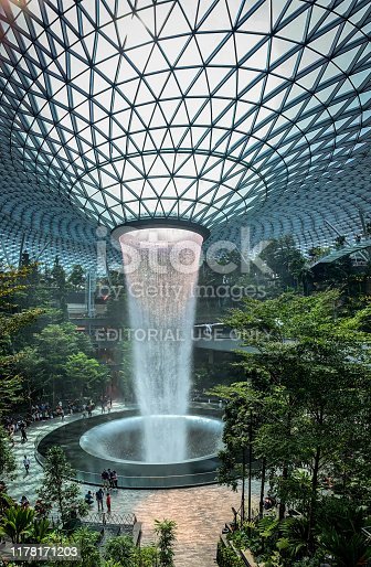 Jewel Changi Airport, Singapore - 5th August, 2019: Visitors tour around the Rain Vortex inside the Jewel area at Changi Airport. It's the world's tallest indoors waterfall at 130 ft in height and surrounded by a four-storey terraced forest. The Jewel complex and waterfall was designed by Moshe Safdie.