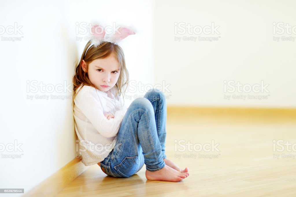 Very angry little girl wearing bunny ears sitting on a floor stock photo
