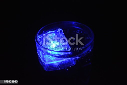 Beautiful photos of glass with carbonated drinks and diode ice cubes.  Glowing ice cubes in wine glasses, original festive background.  Bright and colorful images with light and color effects from plastic ice on batteries.