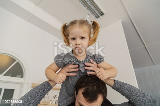 istock A very beautiful girl is sitting on her dad's shoulders and playing, making faces in the New Year's room 1072638508