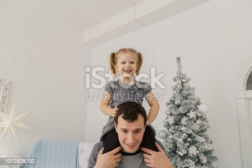 istock A very beautiful girl is sitting on her dad's shoulders and playing, making faces in the New Year's room 1072638702
