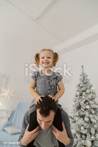 istock A very beautiful girl is sitting on her dad's shoulders and playing, making faces in the New Year's room 1072638782