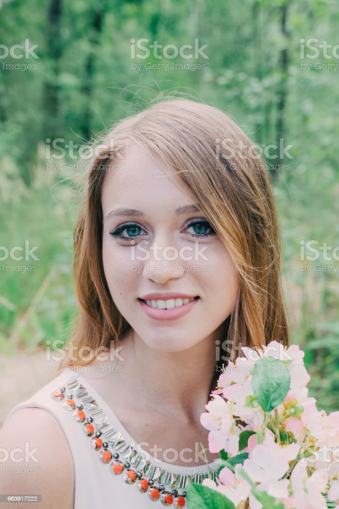 Very beautiful woman in nature surrounded by real flowers - Royalty-free Adult Stock Photo