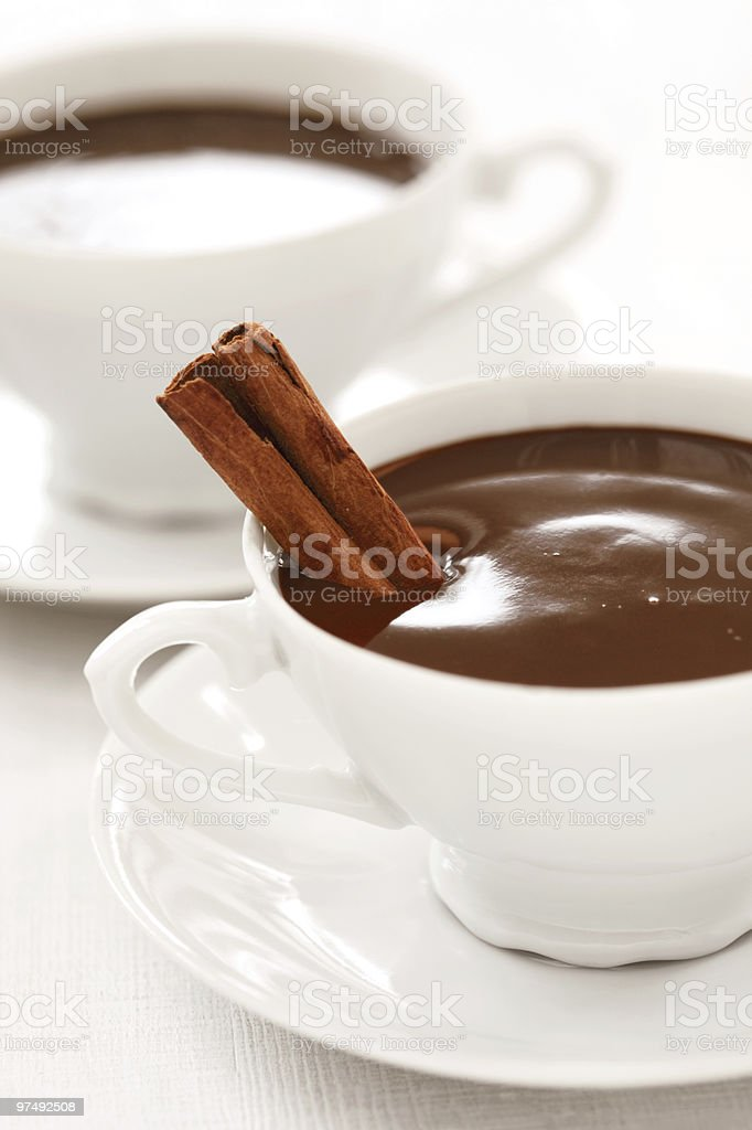 very chocolaty hot chocolate in white cups with cinnamon stick royalty-free stock photo