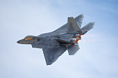 Very close tail  view of a F-22 Raptor against clouds, with afterburners on