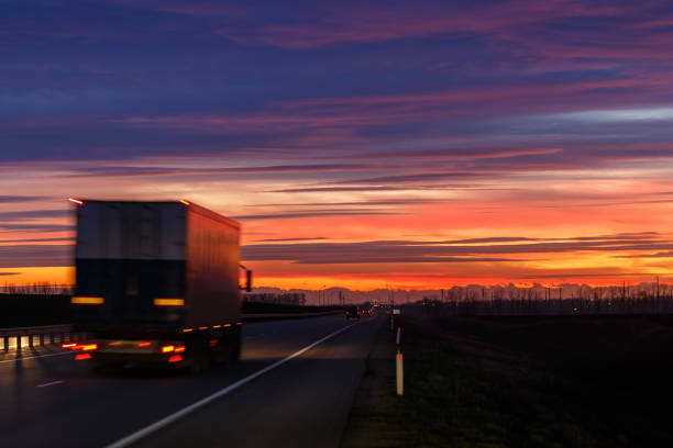 A very colorful sunset and a moving (blurred) truck on an asphalt road stock photo