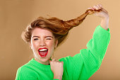 Beautiful young girl pulls itself on the side of curly hair. Girl is wearing a green sweater and smiling. Homeliness. Easy stuff. Casual style.