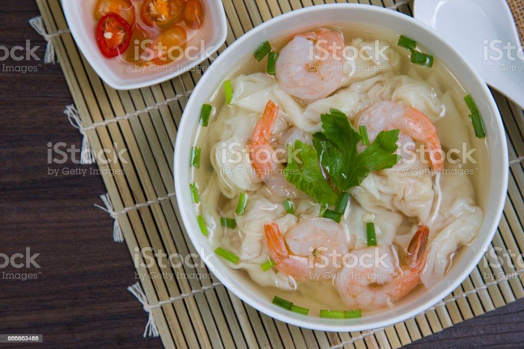 Wonton de camarão delicioso e sopa de carne de porco picada (bolinho) em branco tigela na mesa de madeira / selecionar imagem de foco - foto de acervo