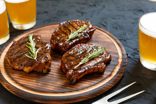 Very delicious steak BBQ and beer in glasses on a black stone background stock photo