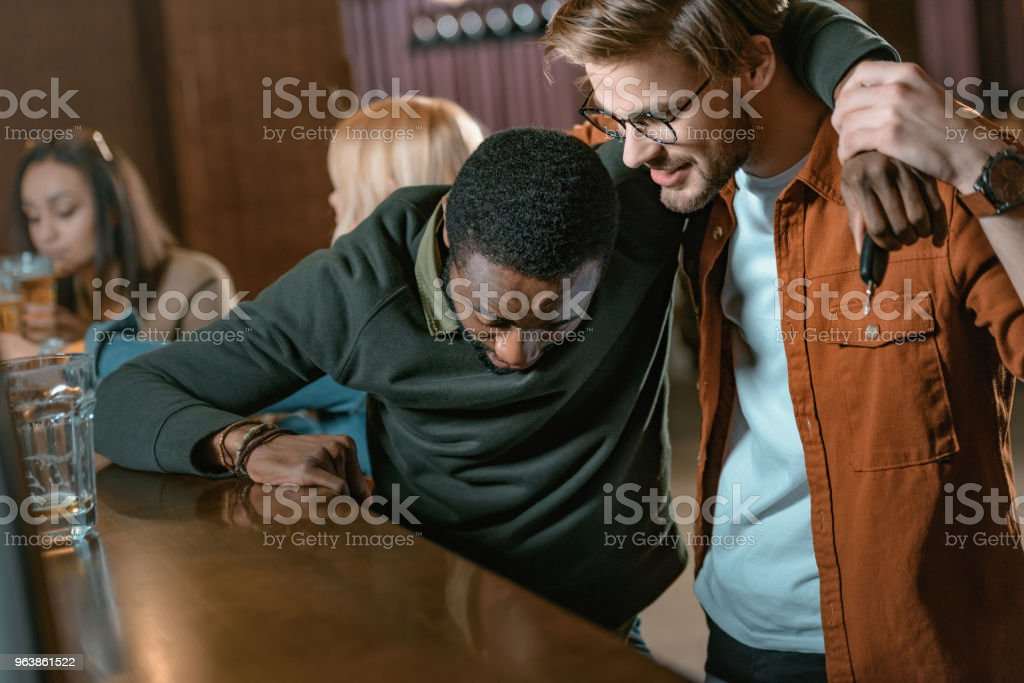 very drunk african american man at bar with friends - Royalty-free Adult Stock Photo