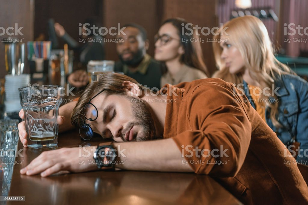very drunk young man at bar with friends - Royalty-free Adult Stock Photo