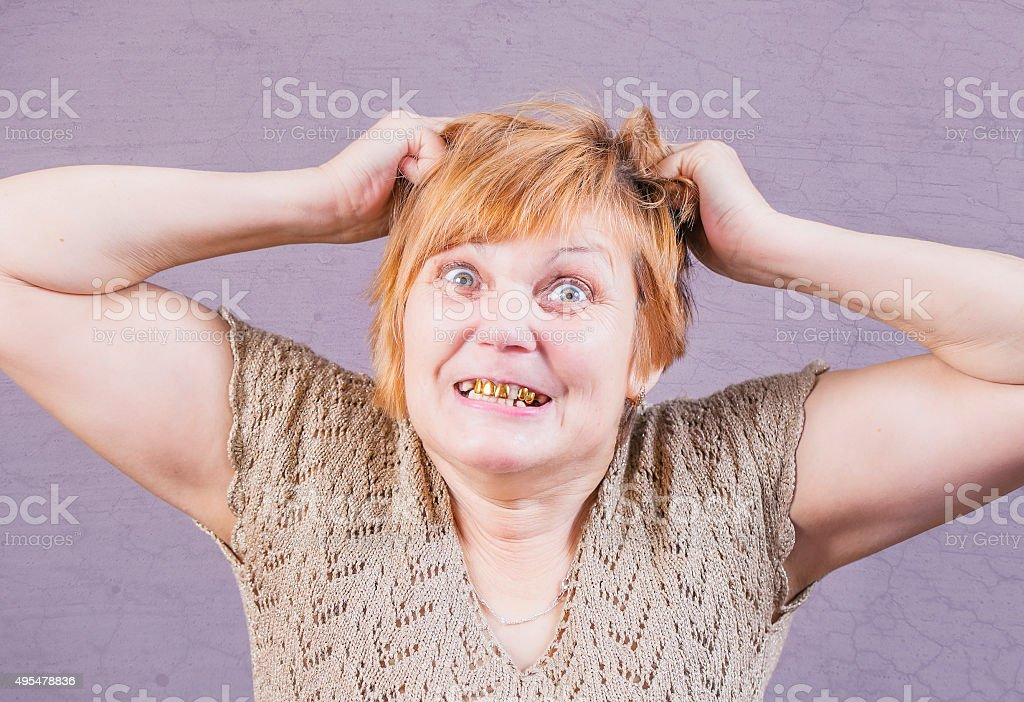 Very emotional angry woman with gold teeth. stock photo
