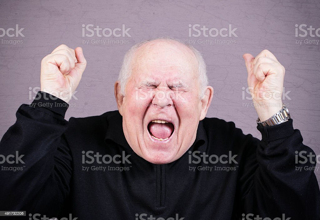 Very emotional old man screams on a gray background. stock photo