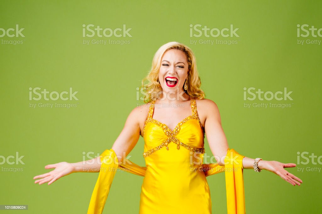 A very excited  blonde  in yellow evening gown with arms out, isolated on green studio background stock photo
