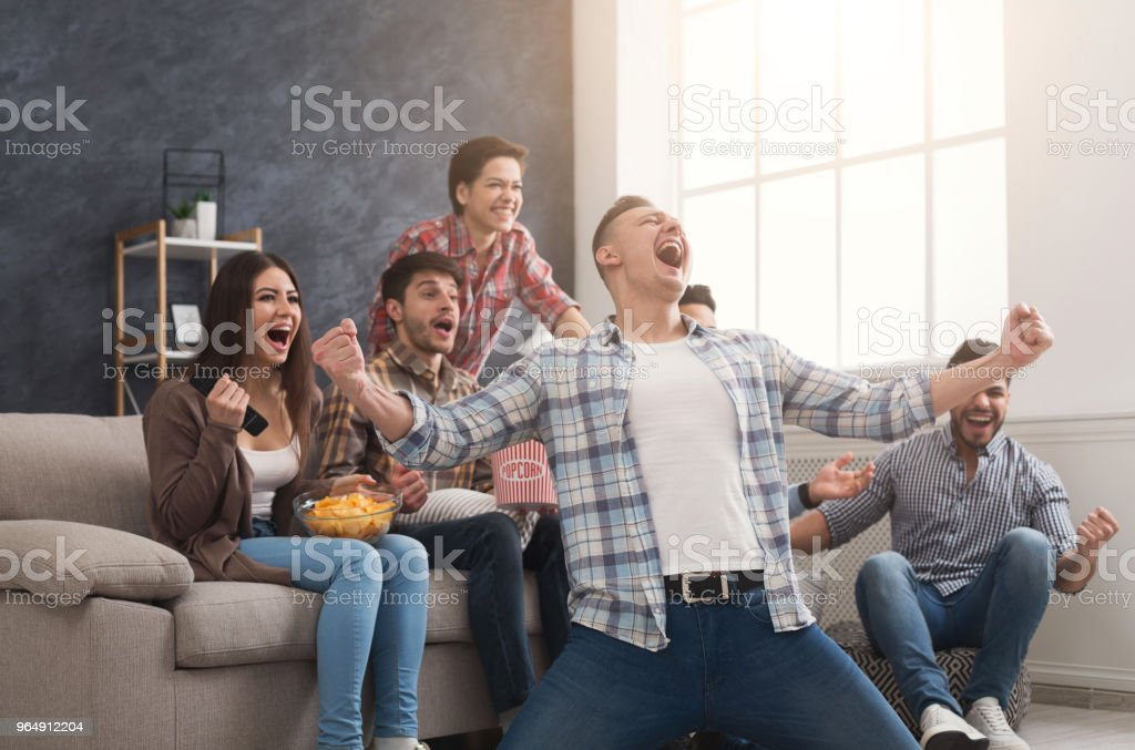 Very excited friends watching football match at home royalty-free stock photo