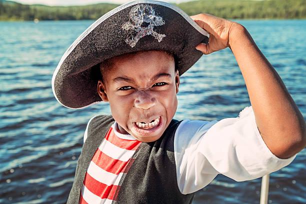 sehr ausdrucksstark african-american kind angezogen wie piraten auf den see. - kleine jungen kostüme stock-fotos und bilder