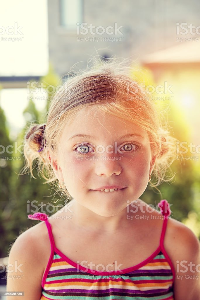 Very expressive little girl biting her lips outdoors. royalty-free stock photo