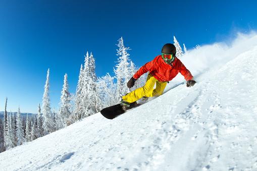 Very fast snowboarder slides at ski slope