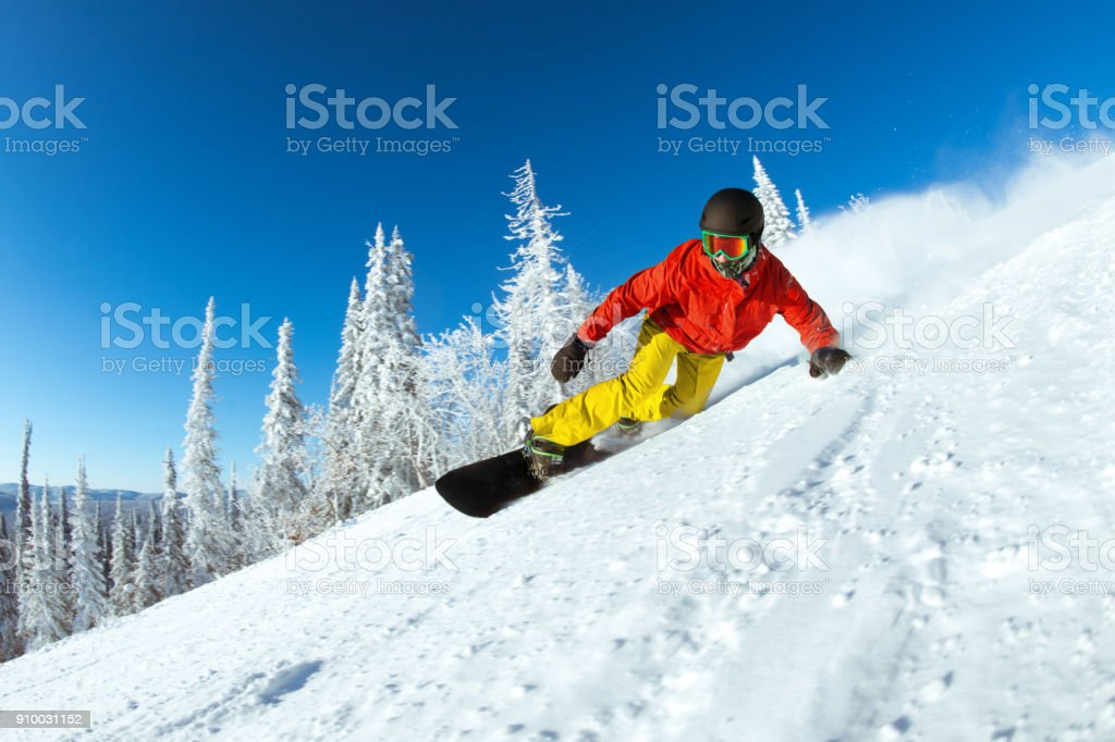 Very fast snowboarder slides at ski slope stock photo