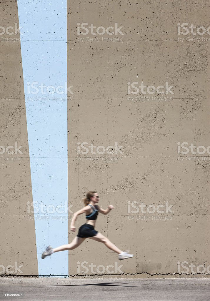 Very fit woman runs and jumps high stock photo