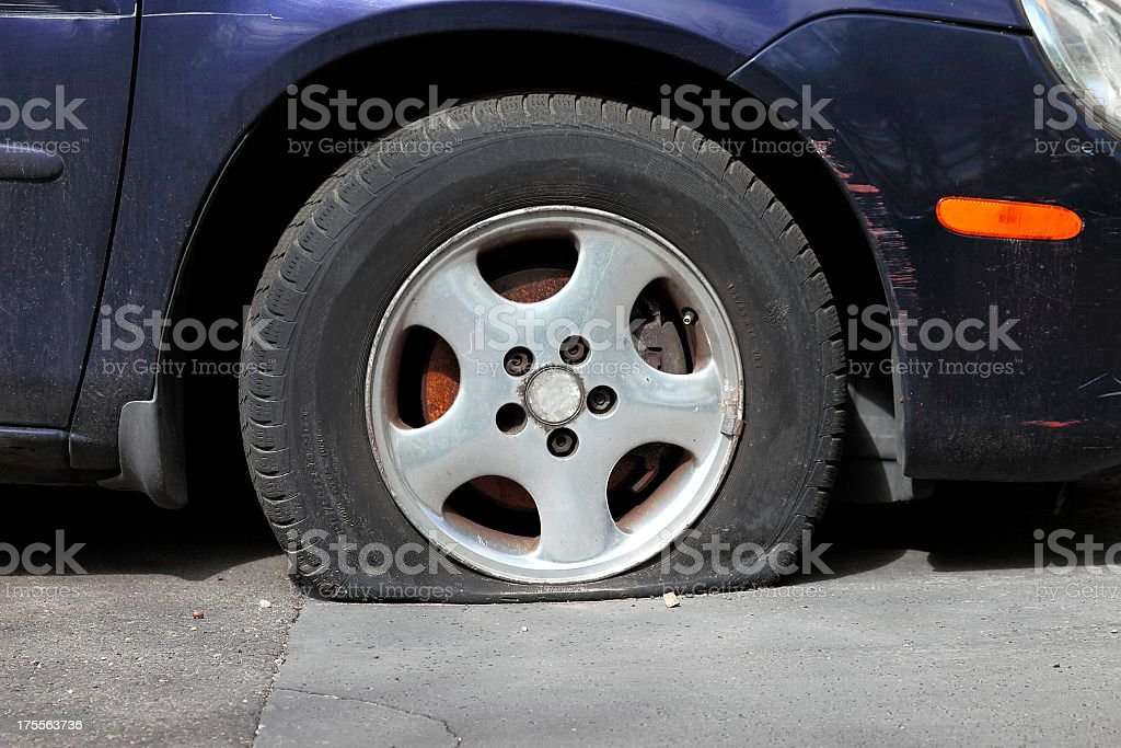 Very flat tire on blue sedan parked on concrete driveway stock photo