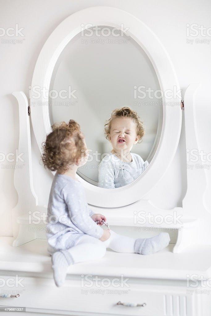 Sehr Lustige Baby Mädchen Blick Auf Ihr Spiegelbild Im Spiegel Stock