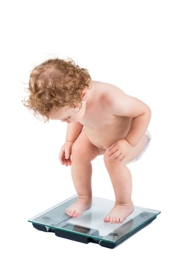istock Very funny baby watching her weight, isolated on white 478026805