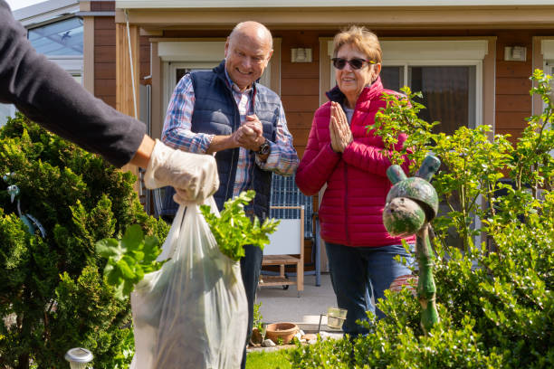 very grateful happy senior couple waiting for food delivery in their garden during covid-19 stock photo