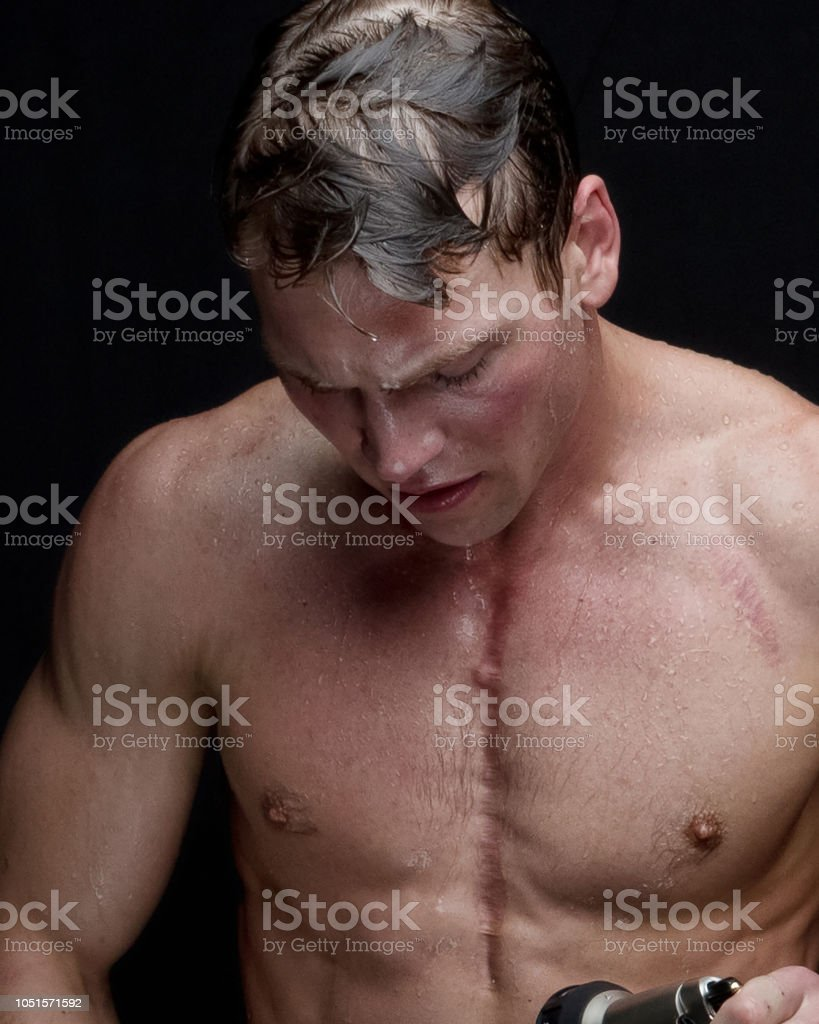 Very handsome man, taking a shower and is wet stock photo
