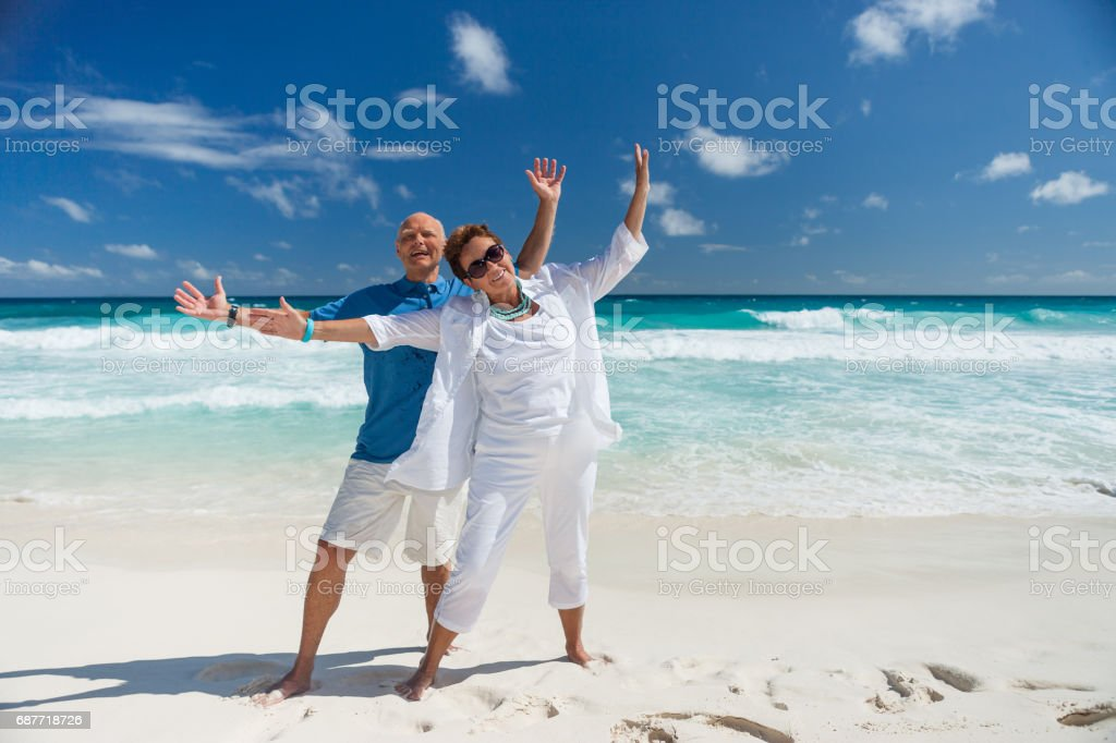 very happy active senior couple on sand beach stock photo