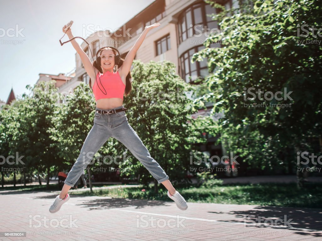 Very happy girl is jumping outside on street. She is keeping her hands and legs wide-opened. Girl is listening to music and holding music player in right hand royalty-free stock photo