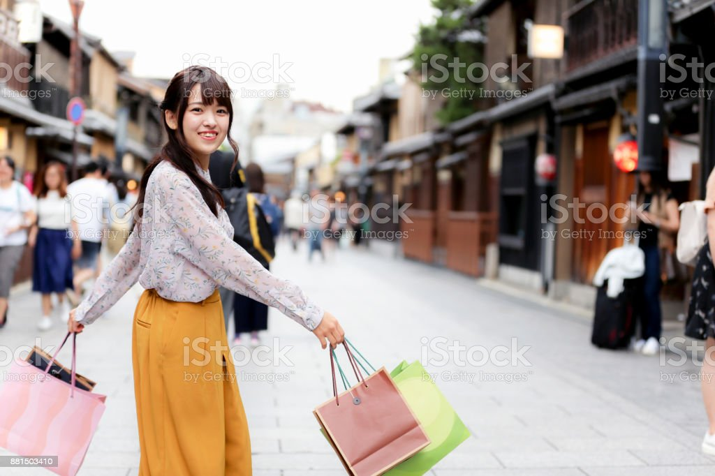 Very happy Japanese girl looking towards the camera with her bags in hand. stock photo