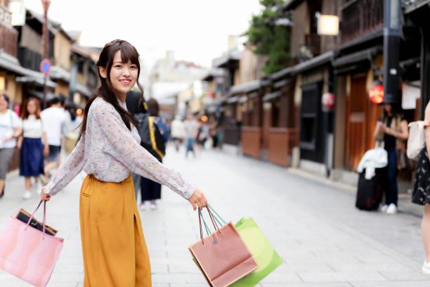 sehr glückliche japanerin mit blick auf die kamera mit ihren taschen in der hand. - taschen von liebeskind stock-fotos und bilder