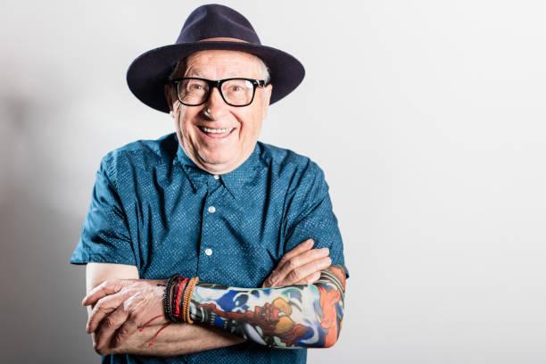 sehr zufrieden seniar mann blick in die kamera und lächelnd, exemplar - alte tattoos stock-fotos und bilder