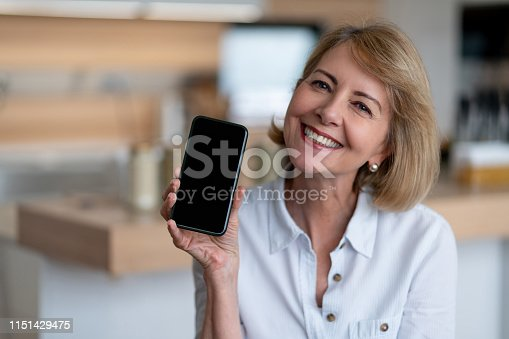 Portrait of very happy senior woman at home using app on her cell phone and showing the display to the camera – lifestyle concepts