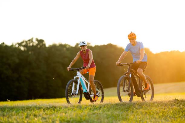 sehr glücklich lächelnd passen sportliche paar auf e-mountainbikes an sonnigen nachmittag im grünland - elektrorad stock-fotos und bilder