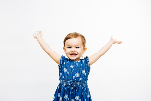 istock very happy toddler girl with arms outstretched up and a victorious smile 1175554094