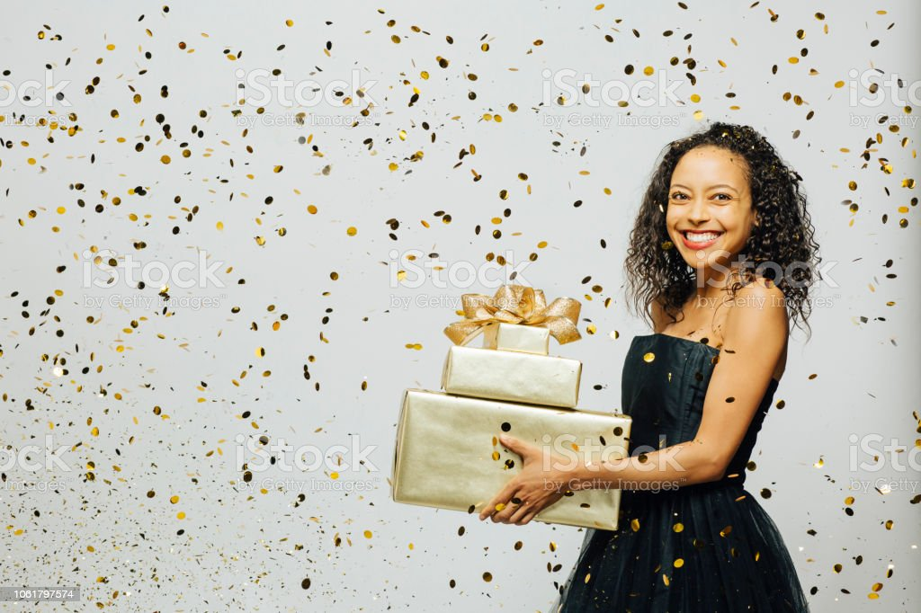 b438b463a2403 Very happy with the gifts, portrait of a woman in a black dress with a big  smile holding gifts as gold confetti are falling - Stock image .
