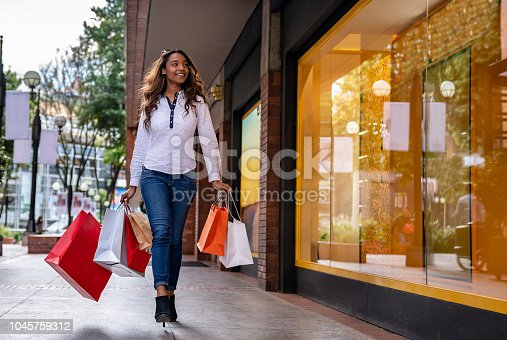 Very happy woman shopping at the mall carrying bags and smiling – lifestyle concepts