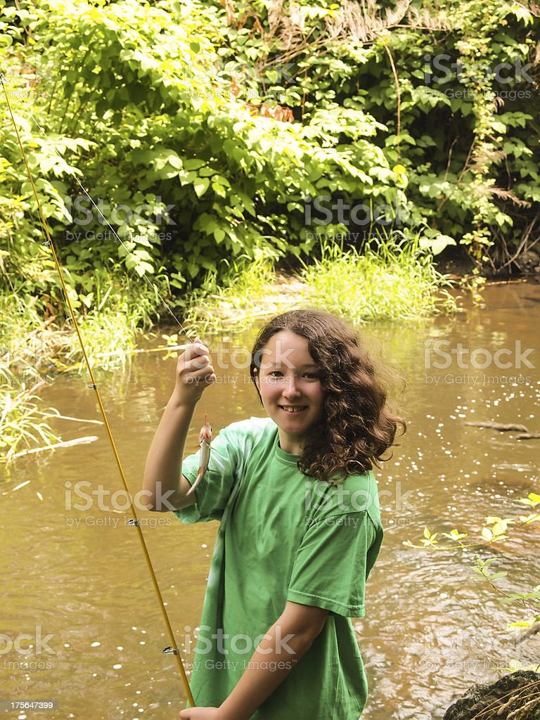 Very happy young girl catches small trout royalty-free stock photo