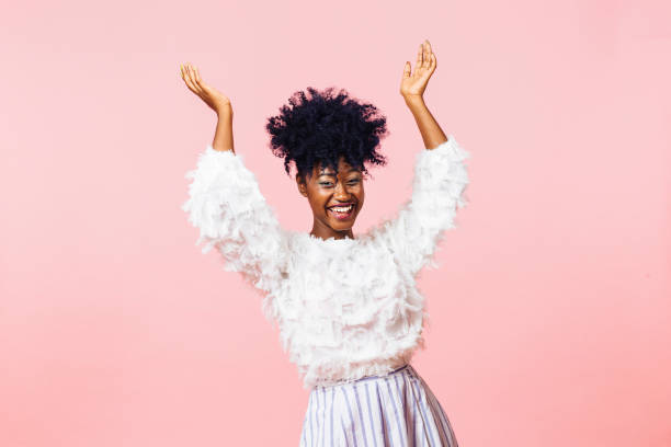 a very happy young woman with both arms up - carlos david stock pictures, royalty-free photos & images