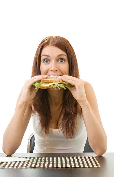 Very hungry gluttonous woman eating sandwich with cheese, isolated stock photo
