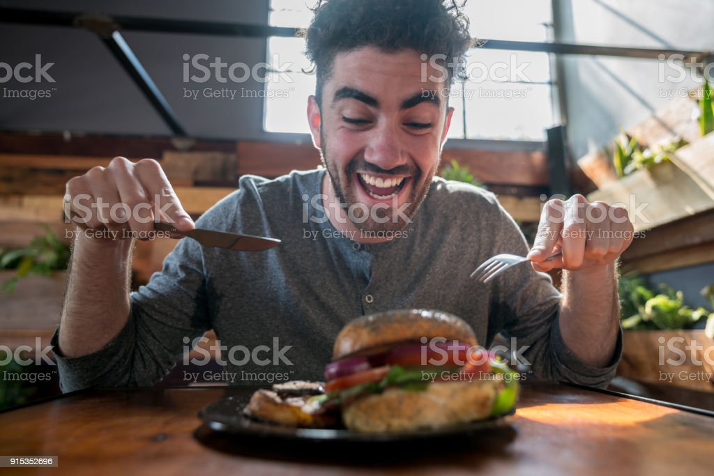 Very hungry young man diving into his burger using cutlery stock photo
