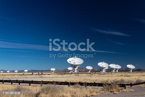 Very Large Array bright white radio antenna dishes against a deep blue sky, New Mexico desert in winter, horizontal aspect