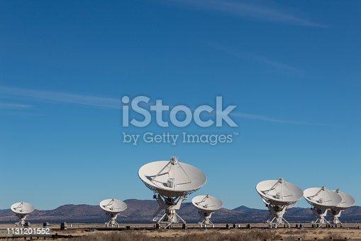 Very Large Array grouping of radio antenna dishes in New Mexico desert, blue sky copy space, horizontal aspect