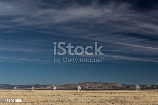 Very Large Array line of radio astronomy observatory telescopes in the New Mexico desert, copy space in blue sky, horizontal aspect