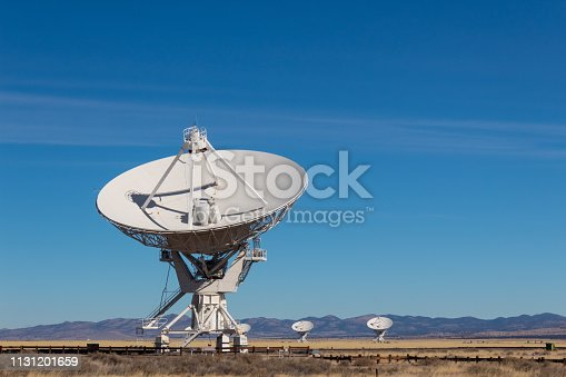 Very Large Array radio antenna dish close with others in distance, blue sky copy space, horizontal aspect