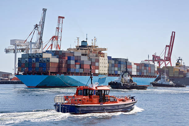 Very Large Container Ship Being Berthed by Two Tugs stock photo