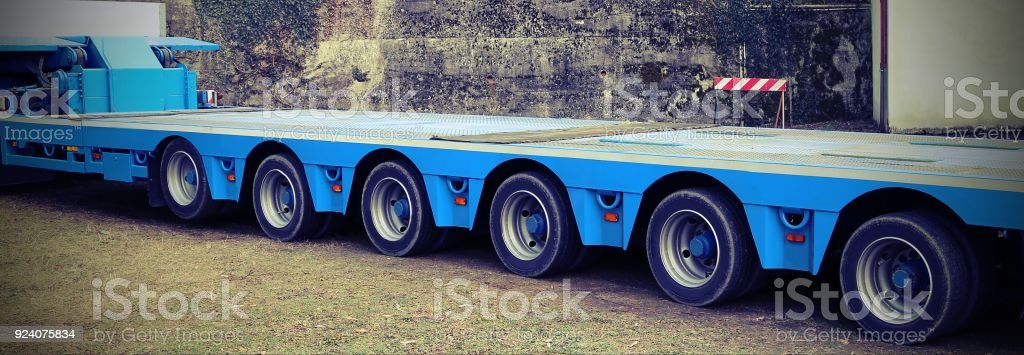 very long blue truck with six  axles of wheels with vintage effect stock photo